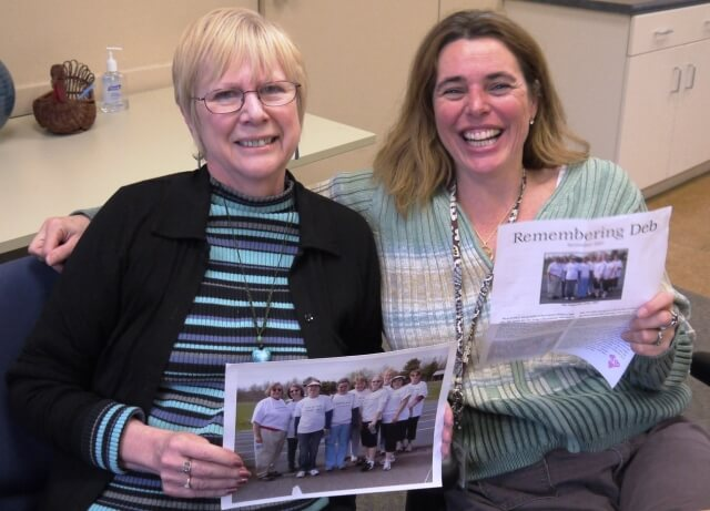 Lesley Bolduc, left, and Jennifer Glover, right, remember their departed friend and coworker as they share stories, photos, and a quilt, reminiscing about her life and creating a memorial walk team in her name, the Clogston Cloggers.