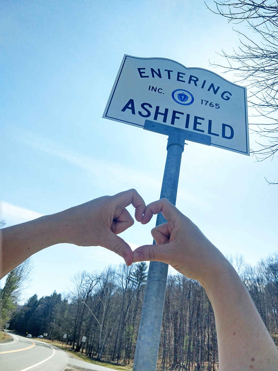 hands making a heart sign in front of a street sign saying entering Ashfield