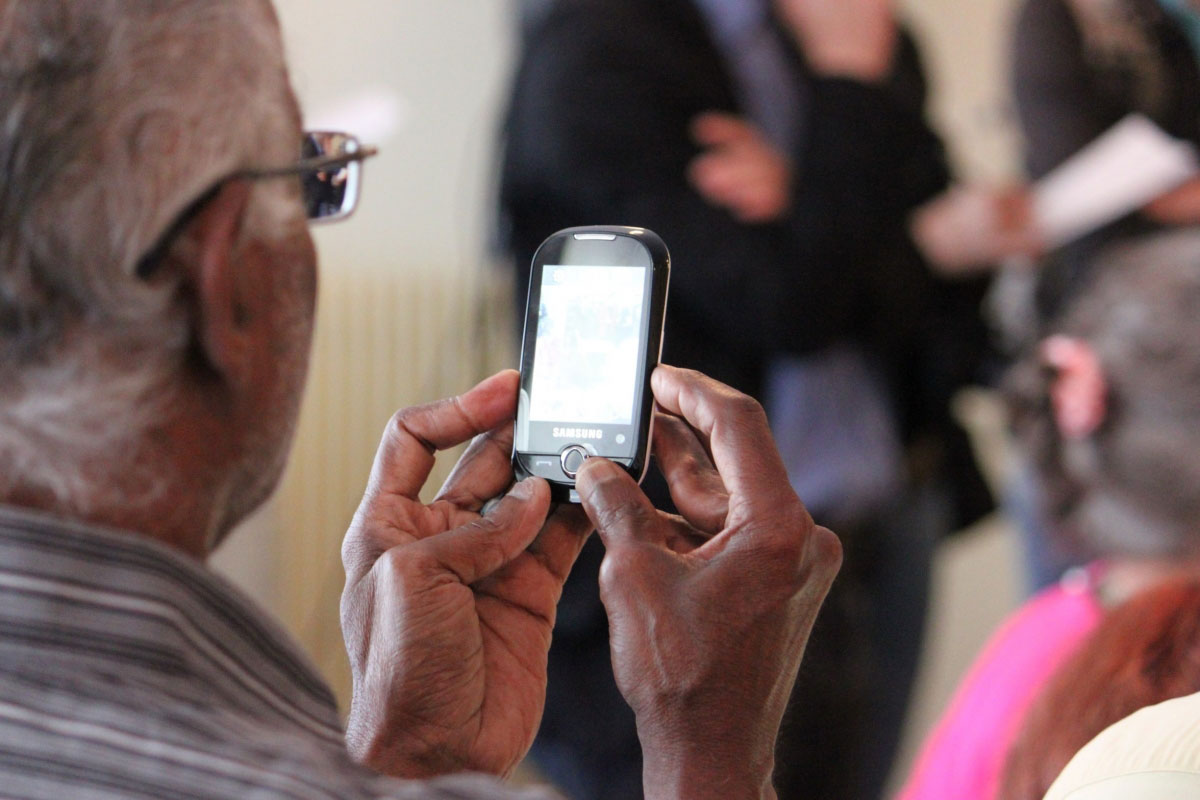 older person (gender unknown) looking at face of phone