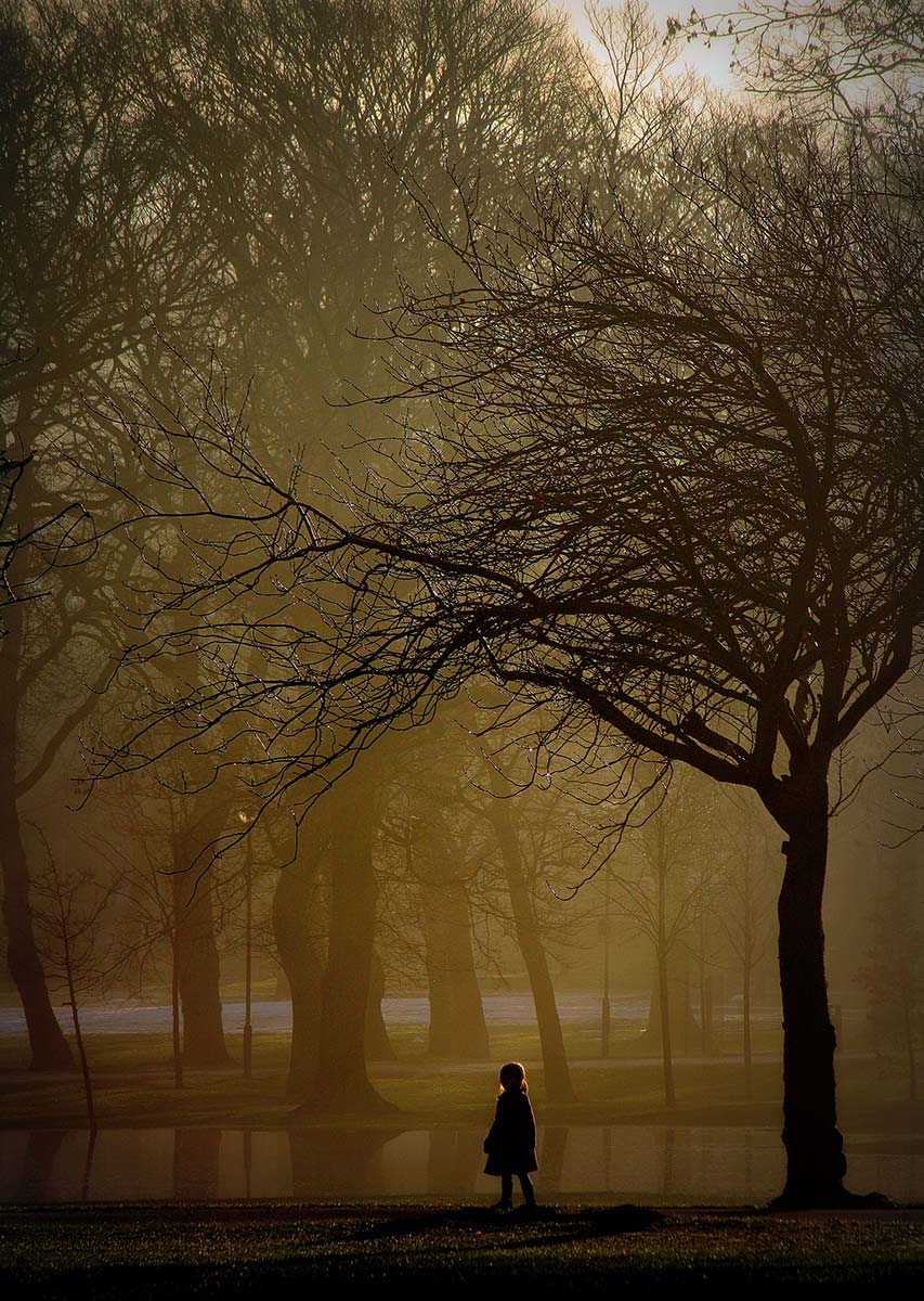 Moody photograph of a girl standing near a tree