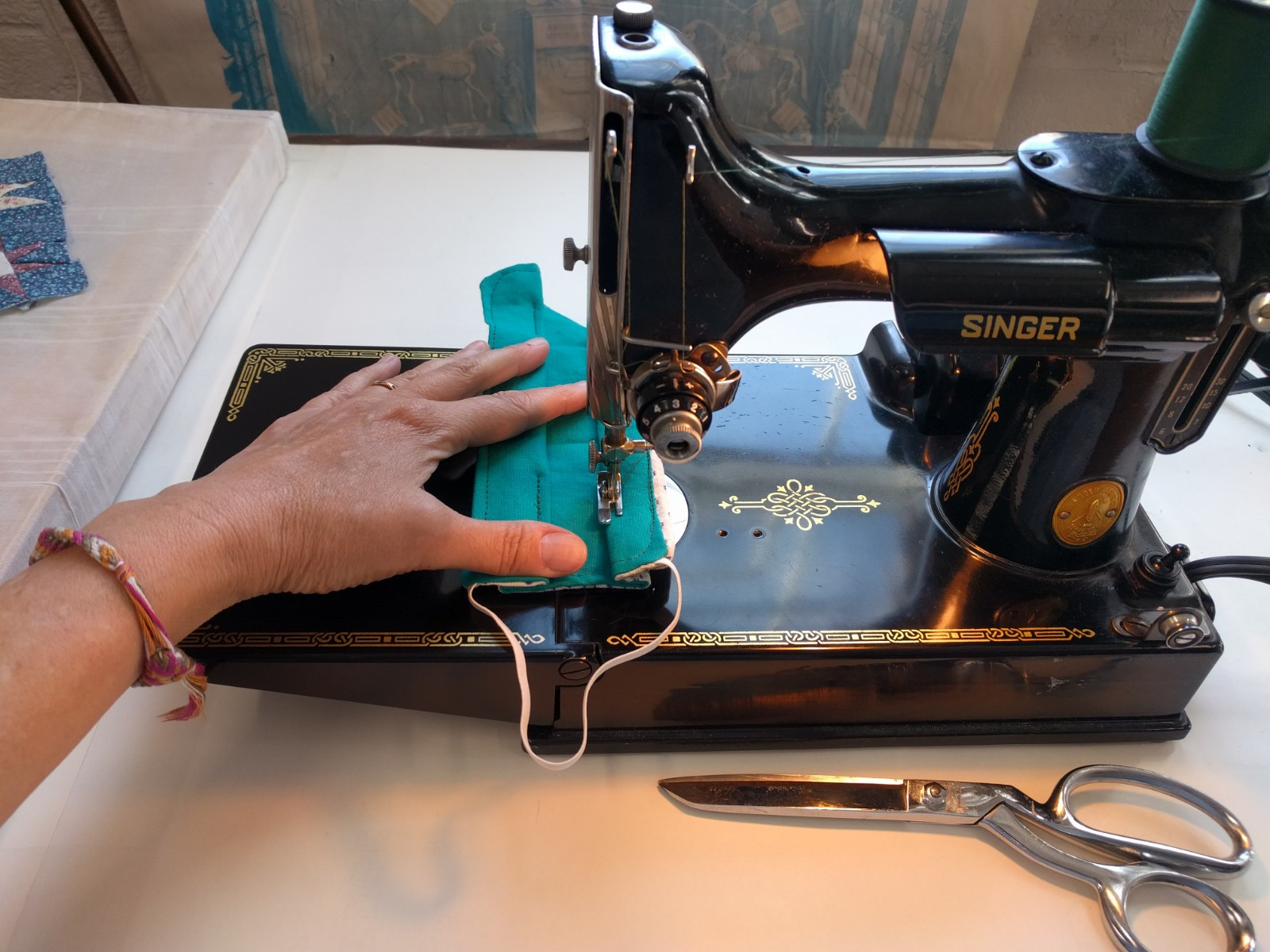 A mask being sewn on an old fashioned sewing machine.
