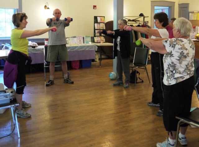 Participants of the Thursday Chair Exercise fitness class at the Bernardston Senior Center take a moment to do some standing exercises with weights.