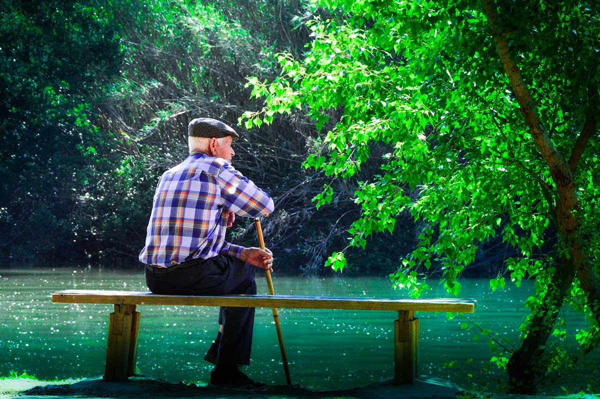 Older gentleman sitting on a bench by a river