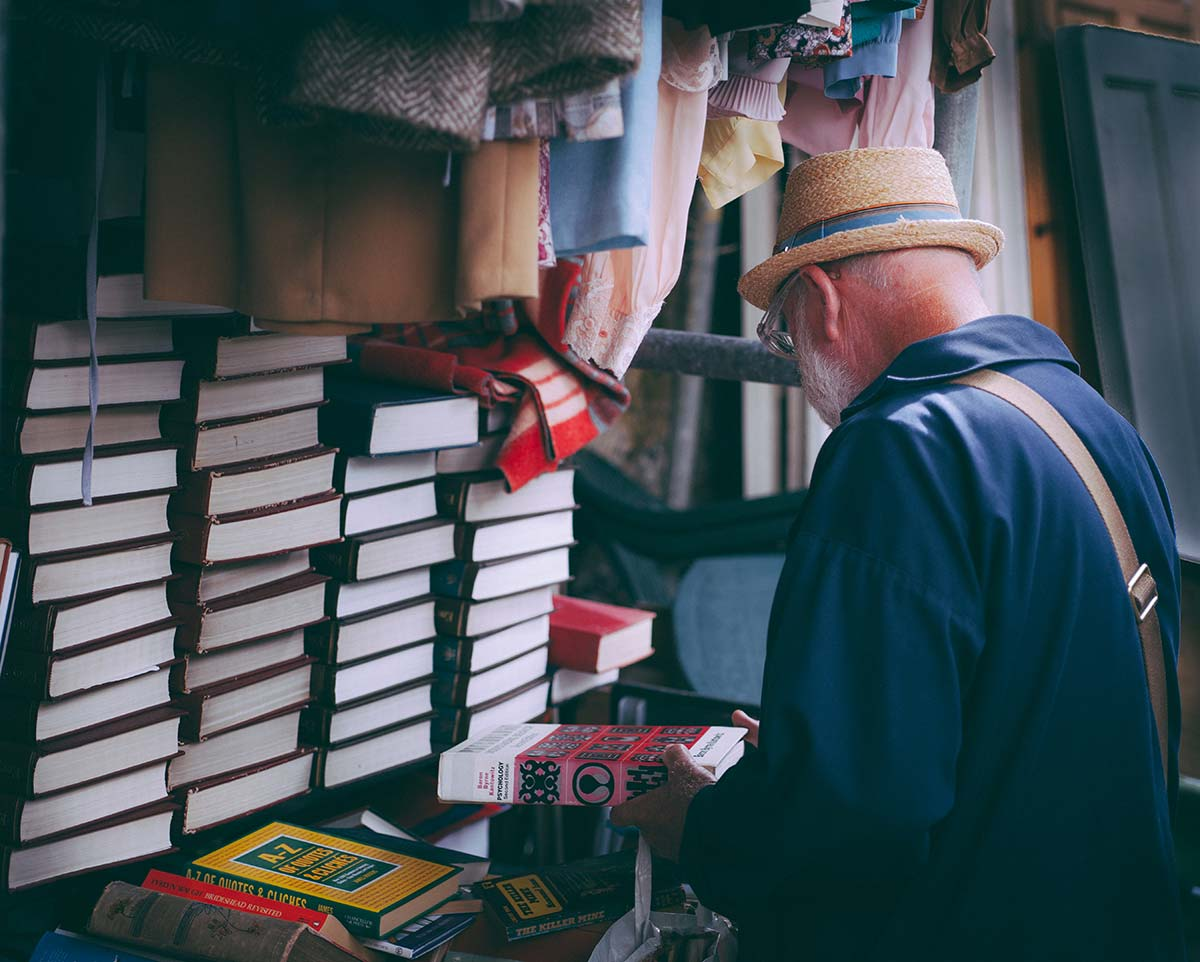 Older gentleman with stacks of used books