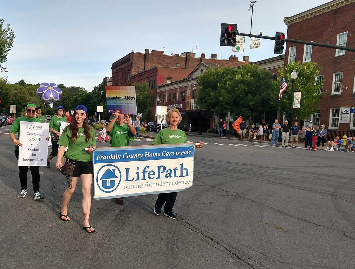LifePath staff holding a banner and signs in parade