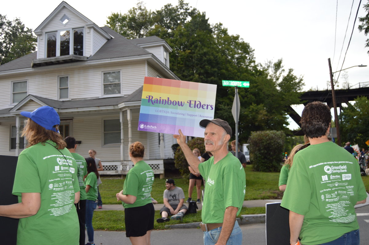 Dave Gott holding Rainbow Elders sign at parade