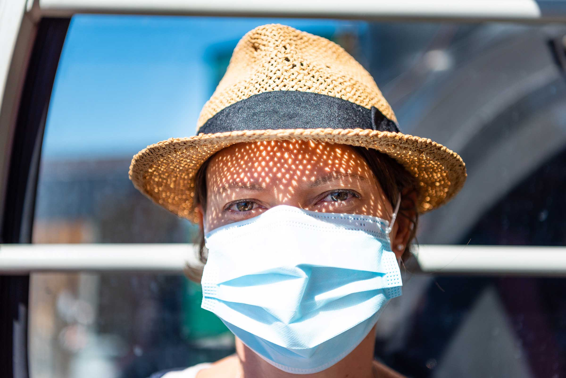 Happy woman wearing surgical mask in sunlight