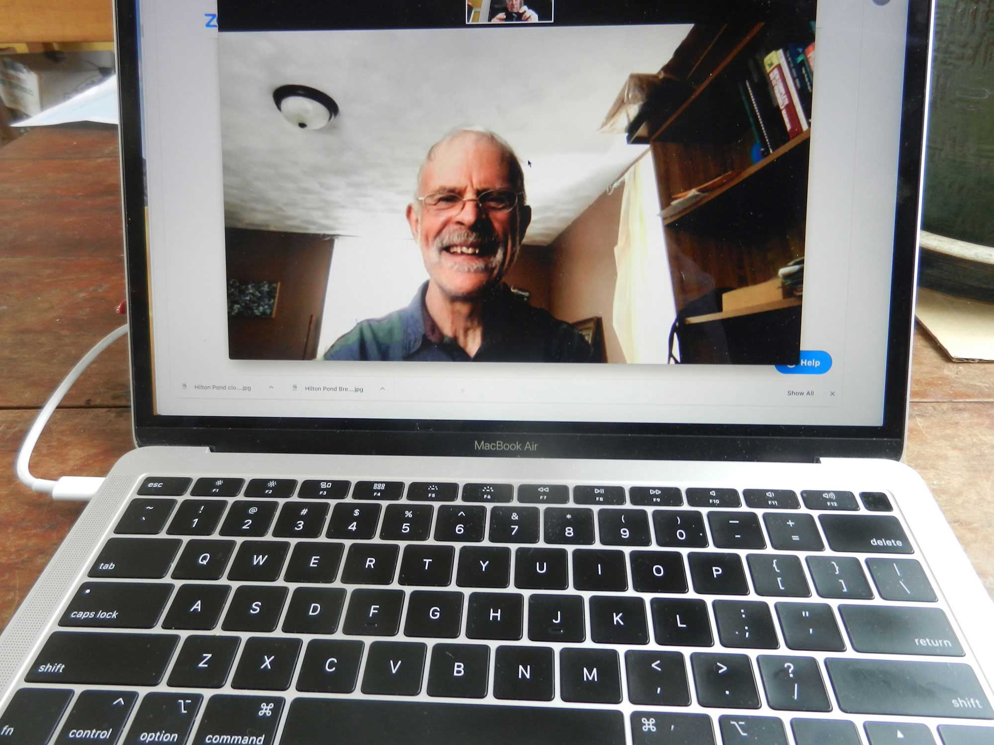 Dave Gott, Rainbow Elders Group Facilitator, smiling from a computer screen facing the camera