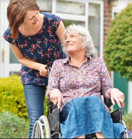 woman smiling at another woman in wheelchair
