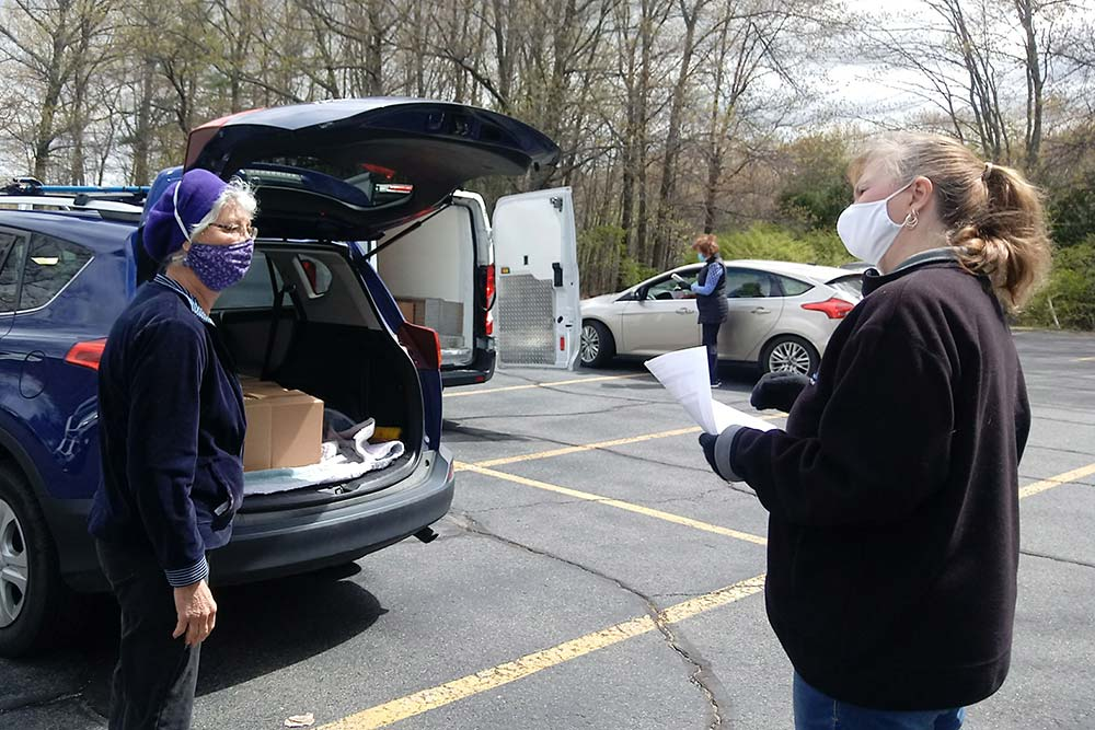 Volunteers wearing masks and talking in a parking lot