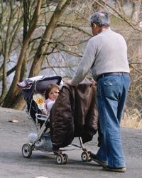 Grandfather pushing grandchild in a stroller.